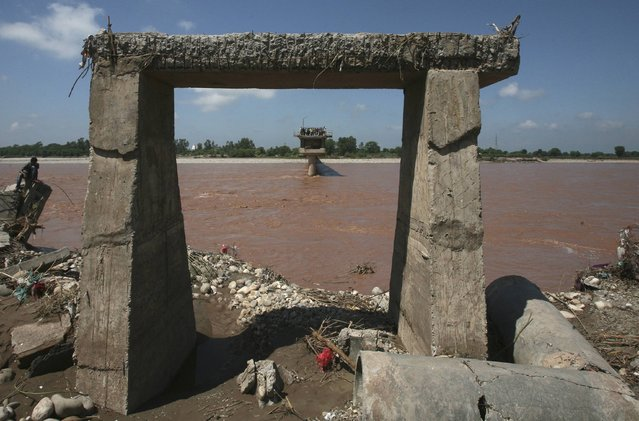 People stand on a damaged bridge which was swept away by floods on the river Tawi in the outskirts of Jammu September 7, 2014. The death toll from serious flooding in Indian-administered Kashmir climbed to 175 on Sunday, with homes, military bases and hospitals inundated in the region's main city Srinagar as the Jhelum river overflowed its banks. About 22 air force helicopters and four aircraft were deployed to evacuate stranded people and to deliver relief. (Photo by Mukesh Gupta/Reuters)