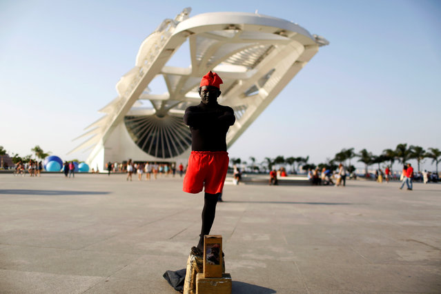 """Erinaldo Cardoso, a 43-year-old street performer, poses for a portrait in front of the Museu do Amanha (Museum of Tomorrow) in Rio de Janeiro, Brazil, July 13, 2016. When asked what he felt about Rio de Janeiro hosting the Olympics, Erinaldo said, """"Nothing will change after the Olympics. Everyone who knows the reality of Rio de Janeiro knows that it is not all happiness"""". He also is concerned that the jobs that have been generated will be lost after the games. (Photo by Pilar Olivares/Reuters)"""