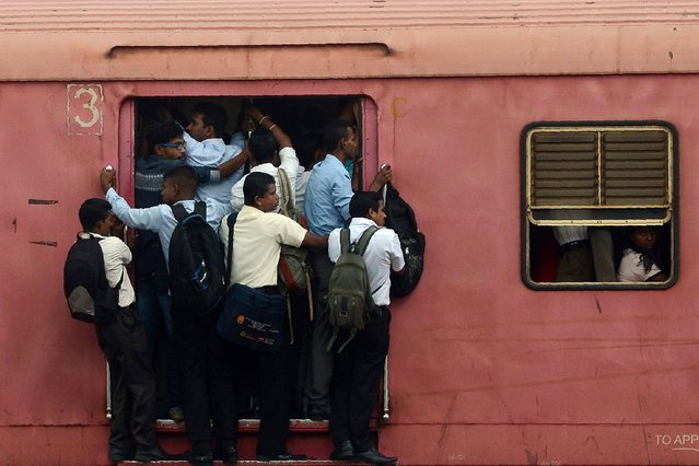 Passengers travel in a train in Colombo on September 19, 2017. Due to its affordability, train travel is a popular mode of transport in this nation of 20 million people. (Photo by Lakruwan Wanniarachchi/AFP Photo)