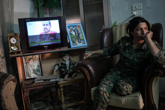 """YPJ soldier Nuhad Kocer, 29, sits near the television; on the left sits a doll dressed in a YPJ uniform with a cigarette in its mouth, nicknamed """"Azadi"""", at a YPJ military base in Til Kocer, Syria, on August 9, 2014.  """"Azadi the doll"""" was named after YPJ soldier Azadi Ristem, pictured in the photo frame on the left, who was killed by sniper fire by Jibhad L'Nasra, a faction group of Al Quaeda. (Photo by Erin Trieb/NBC News)"""