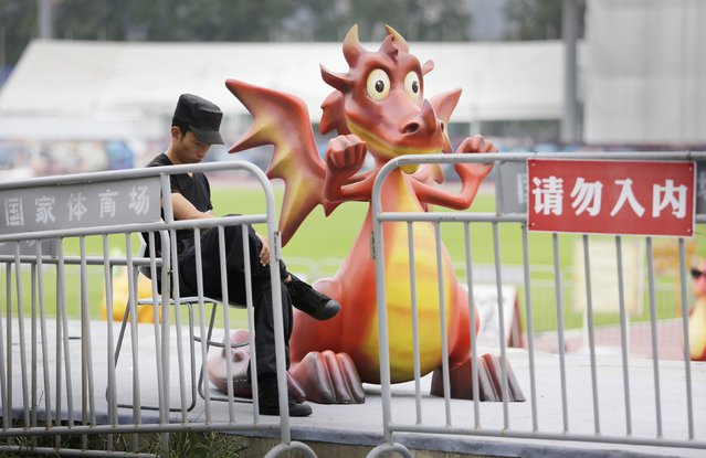 """A security guard looks at his mobile phone next to a sculpture of a dragon character from a cartoon, at an entrance of a movie theme park of """"How to Train Your Dragon"""" in Beijing, September 12, 2014. The red sign reads, """"Do not enter"""". (Photo by Jason Lee/Reuters)"""