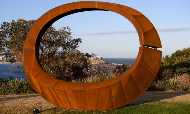 """A winning sculpture """"Orb"""" by David Ball, winner of the $60,000 sculpture award is seen as part of the """"Sculpture by the Sea"""" exhibition near Bondi beach in Sydney on October 19, 2017. """"Orb's faceted sections create angles and curves. Its scale frames the landscape. A split joined by a small orb creates a visual metaphor for a break in unity"""". (Photo by Dean Lewins/AAP)"""