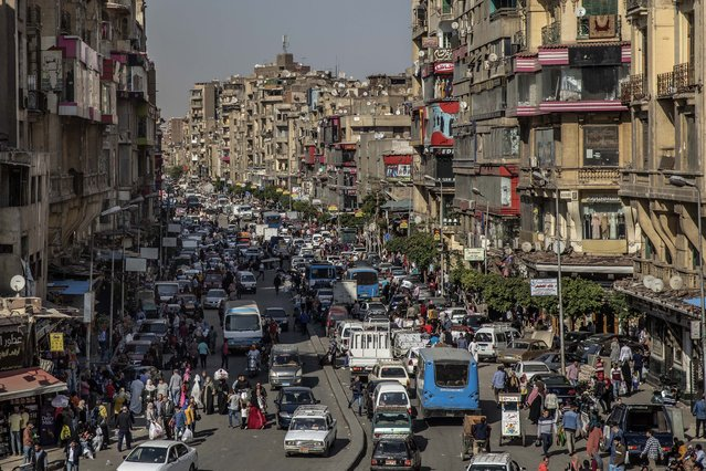 People crowd a street a few hours ahead of curfew in Cairo, Egypt, Tuesday, April 14, 2020. The government has imposed a nationwide curfew from 8 p.m. to 6 a.m due to the coronavirus outbreak. (Photo by Nariman El-Mofty/AP Photo)