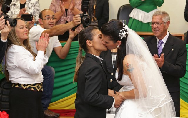Solange Ramires (R) and Sabriny Benites, the only same-s*x couple of 30 couples being married, kiss after they were wed by a judge presiding over the joint ceremony in the Forum of Santana do Livramento, September 13, 2014. (Photo by Edison Vara/Reuters)