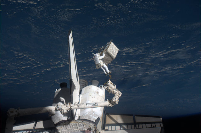Spacewalker Ron Garan rides on the International Space Station's robotic arm with the Earth as a backdrop as he transfers a failed pump module to the cargo bay of space shuttle Atlantis on July 12, 2011. (Photo by Reuters/NASA)