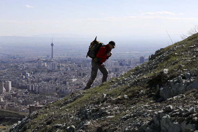 A hiker ascend a foothill of the Alborz mountain range, overlooking the capital Tehran, as he spends his New Year, or Nowruz, holidays, Iran, Tuesday, March 31, 2020. In recent days, Iran which is battling the worst new coronavirus outbreak in the region, has ordered the closure of nonessential businesses and banned intercity travels aimed at preventing the virus' spread. Public parks are closed as well as sport and recreational clubs which were shut previously. (Photo by Vahid Salemi/AP Photo)