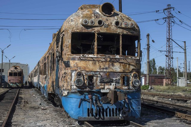 A man walks near a destroyed train at a railway station in the town of Ilovaysk, eastern Ukraine, September 19, 2014. (Photo by Marko Djurica/Reuters)