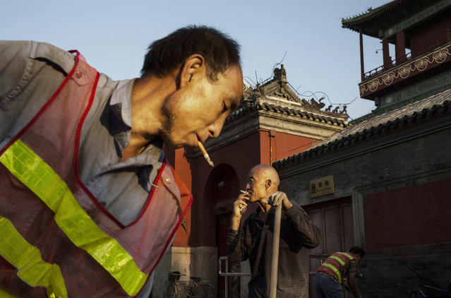 Chinese construction laborers work at the site of a new park in the area around the Drum Tower on September 18, 2014 in central Beijing, China. (Photo by Kevin Frayer/Getty Images)
