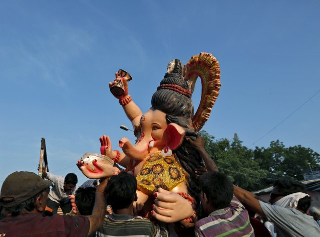 Devotees carry an idol of Hindu elephant god Ganesh, the deity of prosperity, while it is carried to a place of worship in Ahmedabad, India, September 16, 2015. (Photo by Amit Dave/Reuters)