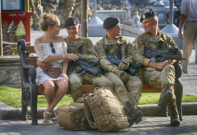 A soldier shares a tender moment with his girlfriend while other soldiers rest during a rehearsal of a military parade a few days before the Independence Day in Kiev, Ukraine, Monday, August 22, 2016. Ukraine to mark the 25th anniversary of the Independence Day on August 24. (Photo by Efrem Lukatsky/AP Photo)