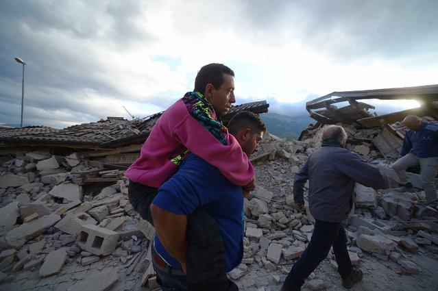 residents help each other among damaged buildings after a strong heartquake hit Amatrice on August 24, 2016. (Photo by Filippo Monteforte/AFP Photo)