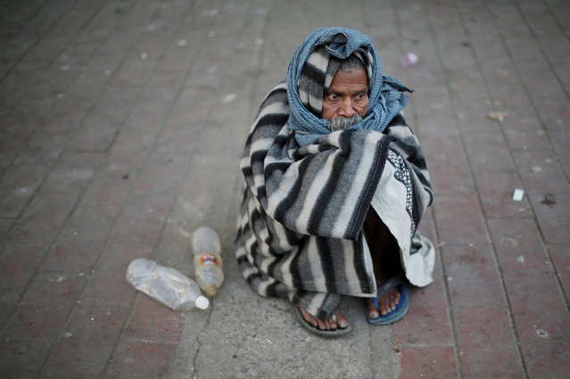 A man is covered in a quilt to keep himself warm as he sits on a pavement on a cold winter morning in New Delhi, India November 22, 2017. (Photo by Adnan Abidi/Reuters)