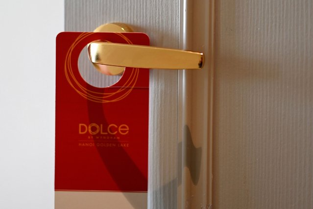 A placard hangs on a room's doorknob at the newly-inaugurated Dolce Hanoi Golden Lake hotel, the world's first gold-plated hotel, in Hanoi on July 2, 2020. (Photo by Manan Vatsyayana/AFP Photo)