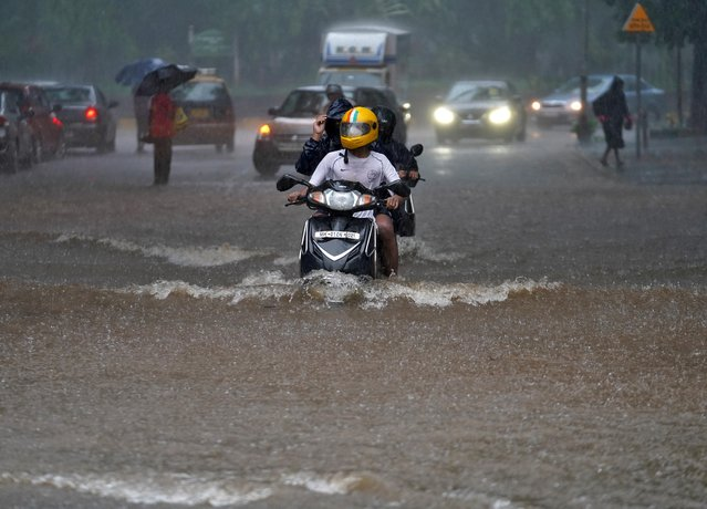 People ride their scooters through a water-logged road during heavy rains in Mumbai, India, July 4, 2020. (Photo by Hemanshi Kamani/Reuters)