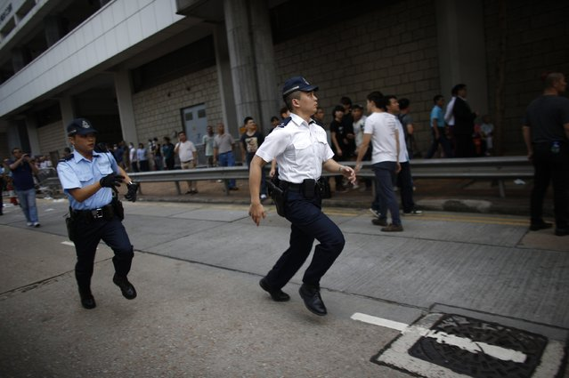 Police officers run towards a confrontation between pro-democracy protester and anti-Occupy Central protesters at the main protest site in Admiralty in Hong Kong October 13, 2014. (Photo by Carlos Barria/Reuters)