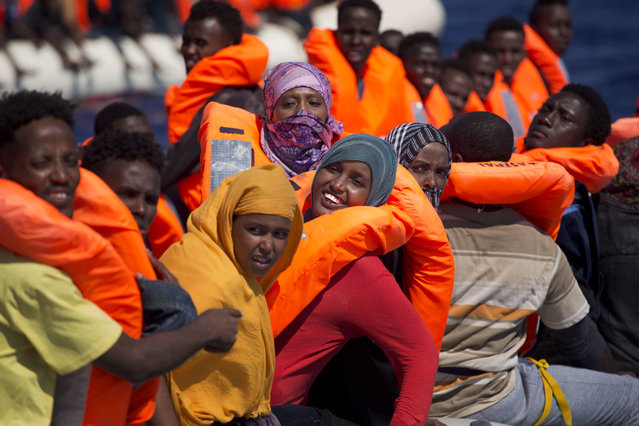 Migrant women smile on board of a dinghy as they sail at the Mediterranean sea toward the Italian coasts, about 17 miles north of Sabratha, Libya, Sunday, August 28, 2016. European nations have tightened border controls, shut down the Balkan route used by hundreds of thousands of people, negotiated an agreement with Turkey to curb new arrivals and taken other measures to curb the influx of migrants. But many problems still remain with Europe's uneven response to the crisis. (Photo by Emilio Morenatti/AP Photo)