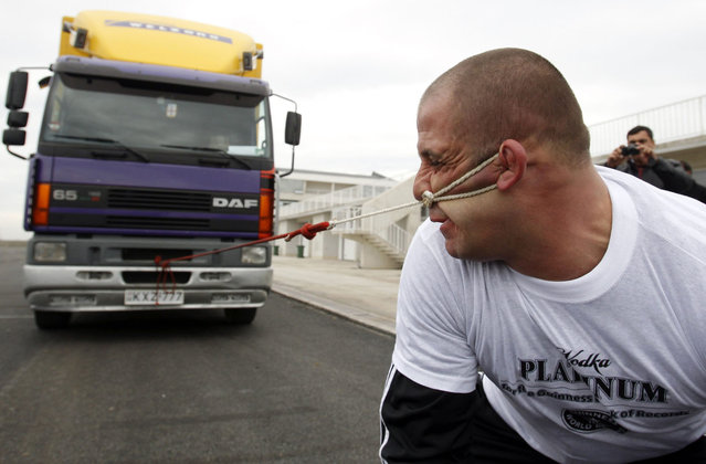 Lasha Pataraia pulls an eight-ton truck with his ear during a test event in Rustavi outside Tbilisi November 14, 2012. The 32-year-old sportsman will attempt to break a record registered by the Guinness Book of World Records by the end of the month, according to organisers. REUTERS/David Mdzinarishvili (GEORGIA - Tags: SOCIETY TPX IMAGES OF THE DAY)