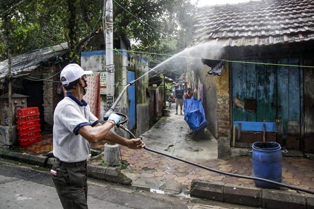 A civic worker disinfects an area inside a containment zone to prevent the spread of the coronavirus in Kolkata, India, Tuesday, July 14, 2020. Several Indian states imposed weekend curfews and locked down high-risk areas as the number of coronavirus cases surged past 900,000 on Tuesday. (Photo by Bikas Das/AP Photo)
