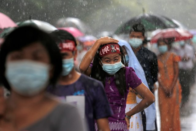People stand in the rain as they wait to enter the Martyrs' Mausoleum during a ceremony for Martyrs' Day in Yangon on July 19, 2020. Myanmar observed the 73rd anniversary of Martyrs' Day on July 19, marking the assassination of independence heroes including Aung San Suu Kyi's father, who helped end British colonial rule. (Photo by Sai Aung Main/AFP Photo)