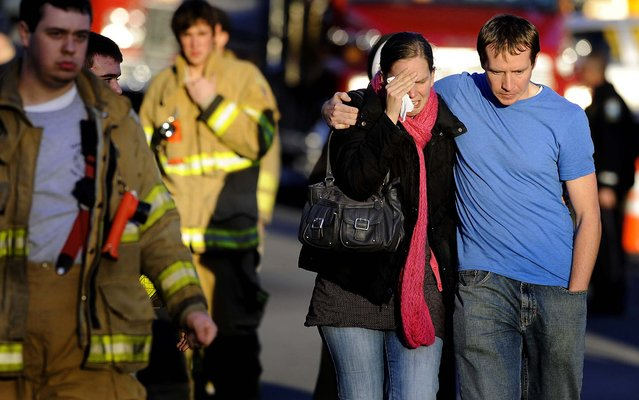 A victim's family leaves a firehouse staging area following the shooting. (Photo by Jessica Hill/Associated Press)
