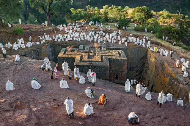 Early-morning worshippers head for the most skilfully executed and best-preserved of the Lalibela churches, Bete Giyorgis (House of St George). It is chronologically probably the last of the churches, and legend has it that it was excavated after St George appeared before King Lalibela and claimed he had been forgotten. Its plan is the shape of a Greek cross, with each arm of equal length, a motif echoed on the roof, which is engraved with a triple Greek cross. (Photo by Ethiopia – The Living Churches of an Ancient Kingdom/The American University in Cairo Press/The Guardian)