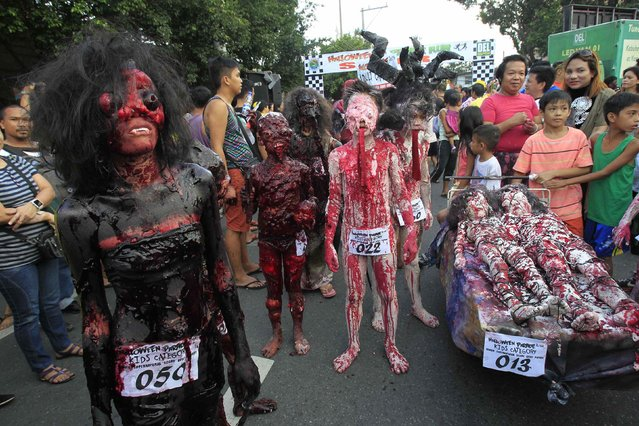 Participants wearing costumes walk along a main street during a Halloween Parade in Marikina city, east of Manila October 30, 2014. (Photo by Romeo Ranoco/Reuters)