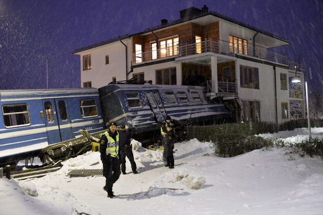 Police officers stand around a local train that derailed and crashed into a residential building in Saltsjobaden outside Stockholm in this picture taken by Scanpix Sweden January 15, 2013. According to local media, a spokesman from Arriva, the company that operates the train line, says the train was stolen by a domestic cleaner, who stole the train for unknown reasons. The cleaner was taken to a hospital after the crash. No residents in the building were injured. (Photo by Jonas Ekstromer/Reuters/Scanpix Sweden)