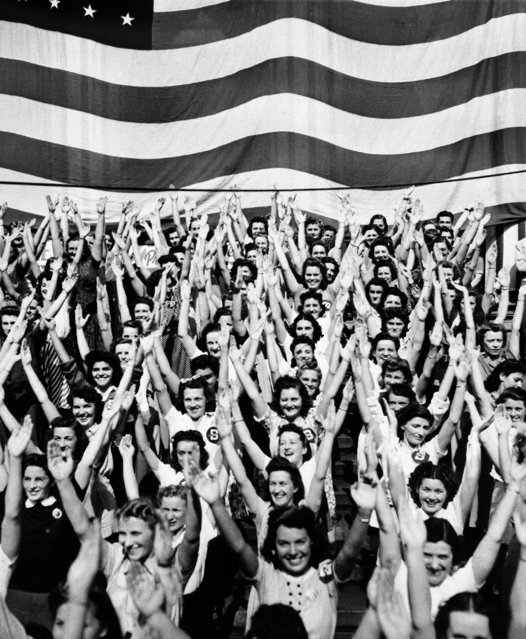 "The Girl Defense Workers, Employees of the RCA Manufacturing Company, raise their arms in the sign of ""V"", the symbol for victory, during a calisthenics drill, October 6, 1941 in Camden to demonstrate how defense workers can keep fit. (Photo by AP Photo)"