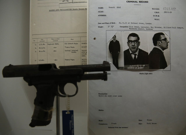 One of Britain's most infamous criminals Ronald Kray's criminal record sheet, along with a hand gun which he used are displayed as part of the Crime Museum Uncovered exhibition at the Museum of London in the City of London, Wednesday, October 7, 2015. (Photo by Alastair Grant/AP Photo)