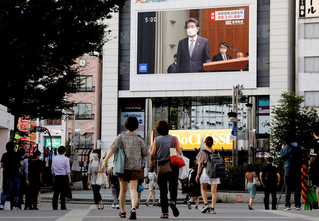 People wearing protective face masks watch the broadcast of a news conference of Japanese Prime Minister Shinzo Abe in Tokyo, Japan, August 28, 2020. (Photo by Kim Kyung-Hoon/Reuters)