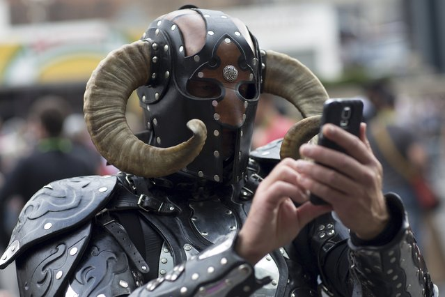 A man in costume uses his cell phone on day two of New York Comic Con in Manhattan, New York, October 9, 2015. (Photo by Andrew Kelly/Reuters)