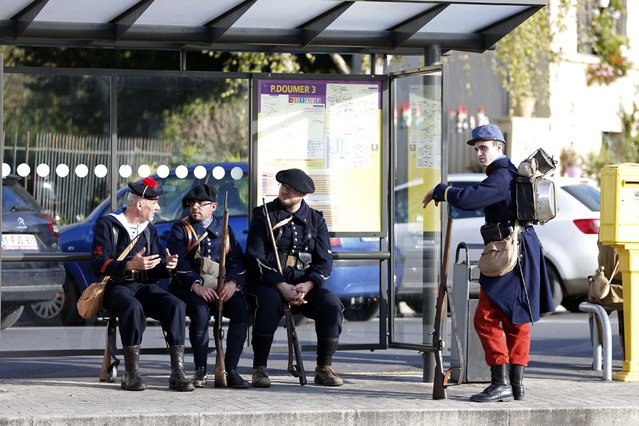 """World War One historical enthusiasts dressed in vintage army uniforms as """"Poilu"""" (French soldier in World War I) take a break at a bus stop before an Armistice Day ceremony to commemorate the end of World War One at Chateau Thierry, eastern France, November 11, 2014. (Photo by Charles Platiau/Reuters)"""