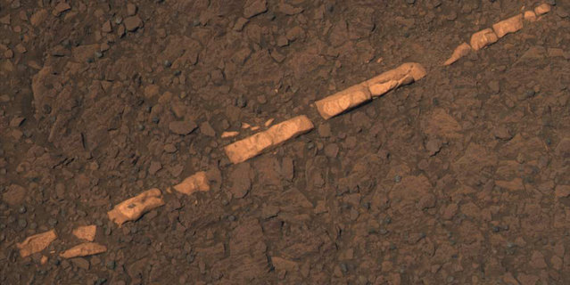 "This color view taken November 7, 2011 of a mineral vein called ""Homestake"" comes from the Pancam on Opportunity, taken on December 7, 2011. The vein is about the width of a thumb and about 18 inches (45 centimeters) long. Opportunity examined it in November 2011 and found it to be rich in calcium and sulfur, possibly the calcium-sulfate mineral gypsum. Homestake is near the edge of the ""Cape York"" segment of the western rim of Endeavour Crater. The view is presented in approximate true color. (Photo by Reuters/NASA/JPL-Caltech/Cornell/ASU/The Atlantic)"