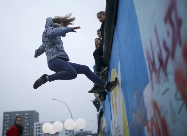 """A young member of the project """"Zirkus Ueberwindet Grenzen"""" (circus without borders) bounces on a trampoline onto the East Side Gallery, the largest remaining part of the former Berlin Wall, next to the installation """"Lichtgrenze"""" (Border of Light) in Berlin November 9, 2014. (Photo by Hannibal Hanschke/Reuters)"""