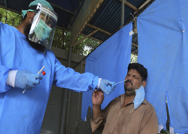 A man reacts while having a nasal swab sample taken at a testing and screening facility for the coronavirus, in a hospital in Karachi, Pakistan, Friday, August 21, 2020. (Photo by Fareed Khan/AP Photo)