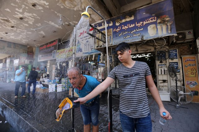 People cool off under a roadside shower as temperatures exceed 45°C in the capital city Baghdad, Iraq on August 08, 2020. (Photo by Murtadha Al-Sudani/Anadolu Agency via Getty Images)