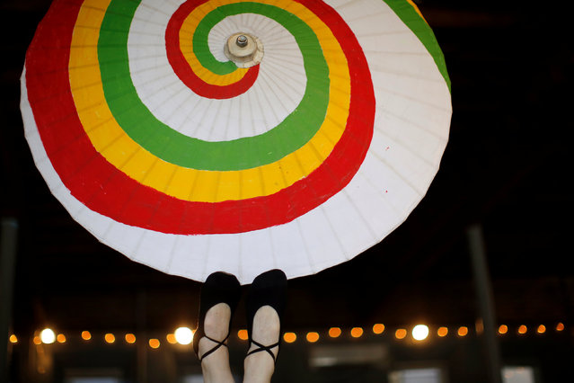 "Tana ""Tank"" Kara balances a parasol on her feet as she practices her foot juggling at the Aloft Loft circus training and teaching school which was converted from a church, in Chicago, Illinois, U.S., September 20, 2016. (Photo by Jim Young/Reuters)"