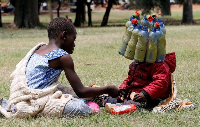"""A child wears plastic bottle waste provided by climate change and environmental activists as they protest marking a global climate action day under the theme """"#AfricaIsNotADumpster"""" at the Uhuru Park's Freedom Corner in Nairobi, Kenya, September 25, 2020. (Photo by Thomas Mukoya/Reuters)"""