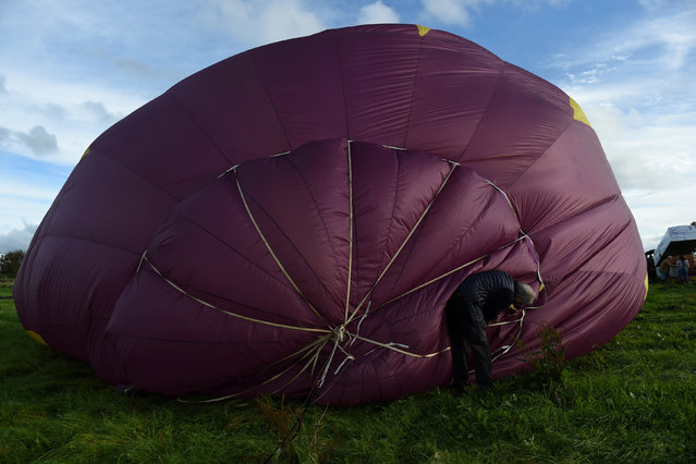 A man inflates a hot air balloon during the Irish hot air ballooning championships in Galway, Ireland September 26, 2016. (Photo by Clodagh Kilcoyne/Reuters)