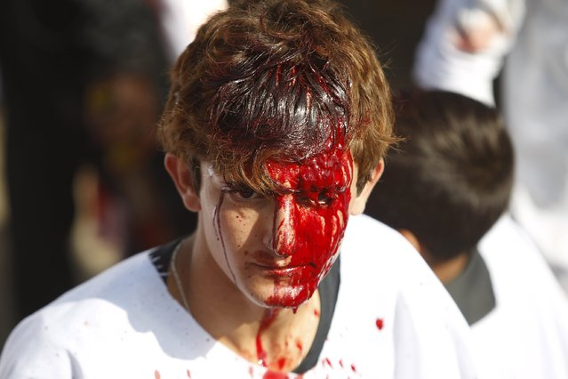 An Iraqi Shi'ite boy looks on as Iraq Shi'ite Muslims gash their foreheads with swords and beat themselves while commemorating Ashura in Baghdad, October 24, 2015. Ashura, which falls on the 10th day of the Islamic month of Muharram, commemorates the death of Imam Hussein, grandson of Prophet Mohammad, who was killed in the seventh century battle of Kerbala. (Photo by Ahmed Saad/Reuters)