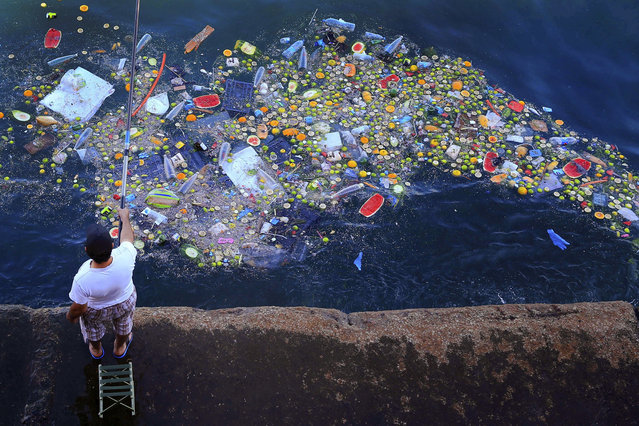 A man holds a fishing rod as floating trash hits the coastline of the Mediterranean Sea in Beirut, Lebanon, Thursday, September 29, 2016. (Photo by Hassan Ammar/AP Photo)