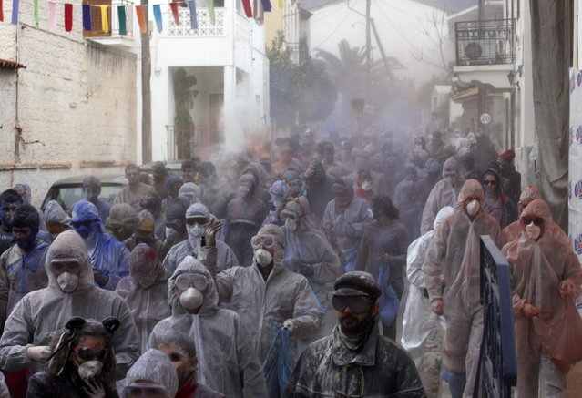 "Revellers celebrate ""Ash Monday"" by participating in a colourful ""flour war"", a traditional festivity marking the end of the carnival season and the start of the 40-day Lent period until the Orthodox Easter,in the port town of Galaxidi, some 215 km (134 miles) north west of Athens, March 18, 2013. The revellers ""fight"" by throwing coloured flour, charcoal dust and powder painting until they essentially run out of supplies. (Photo by Yannis Behrakis/Reuters)"