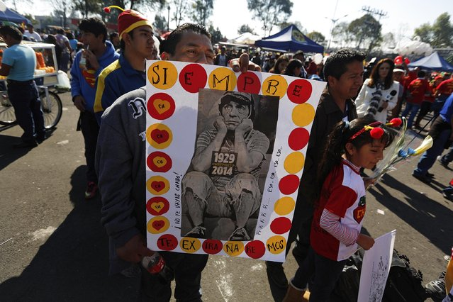 "A man holds a poster with a picture of ""El Chavo del Ocho"", a character created by screenwriter Roberto Gomez Bolanos, as he waits to enter the Azteca stadium for a mass in memory of Gomez Bolanos in Mexico City November 30, 2014. (Photo by Tomas Bravo/Reuters)"
