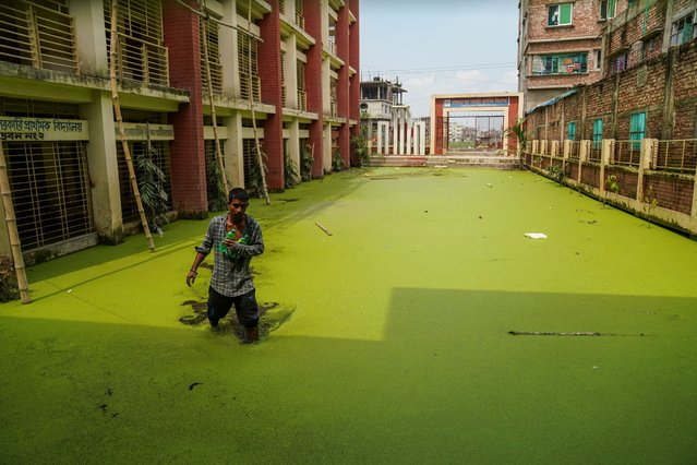 A man walking through stagnant water. Rainwater remains stagnant on ground floor of Kajlapara Government Primary School in Dhaka, Bangladesh, on October 1, 2020. (Photo by Zabed Hasnain Chowdhury/SOPA Images/LightRocket via Getty Images)