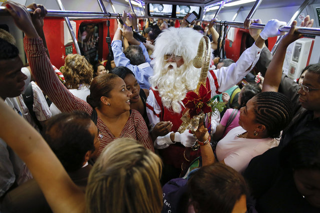 A man dressed as Santa Claus rides a crowded subway train in Sao Paulo, Brazil, Friday, December 5, 2014. This Santa says he'll ride the city's subway trains in December to celebrate the Christmas season. (Photo by Andre Penner/AP Photo)