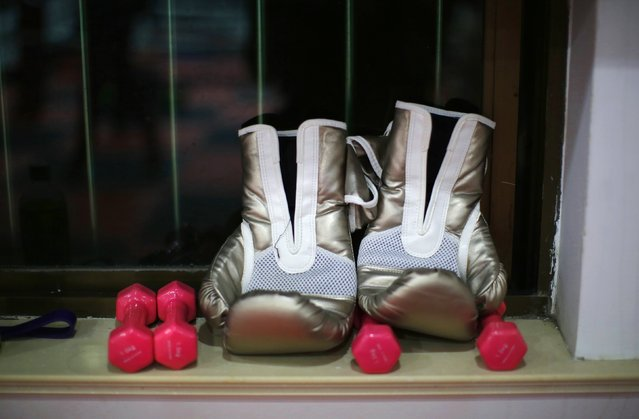 A pair of boxing gloves are seen by a window at Princess Women's Boxing Club in Shanghai December 3, 2014. (Photo by Carlos Barria/Reuters)