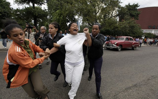 Cuban security personnel detain a member of the Ladies in White group during a protest on International Human Rights Day, in Havana December 10, 2014. Cuban police detained several activists during peaceful demonstrations at a popular Havana square on Wednesday, an annual protest on International Human Rights Day. (Photo by Enrique De La Osa/Reuters)