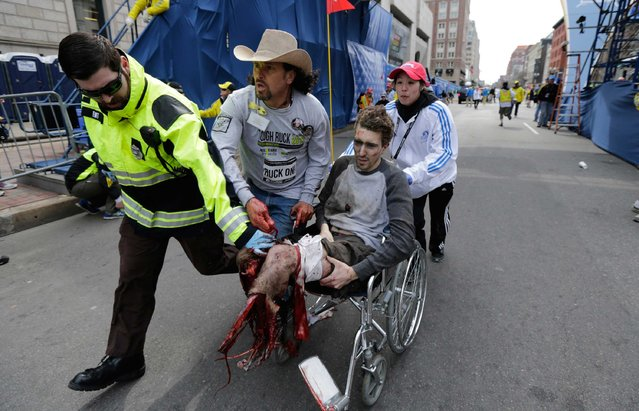 Medical responders run an injured man past the finish line of the 2013 Boston Marathon following two explosions that killed at least two people and injured more than twenty others. (Photo by Charles Krupa/Associated Press)