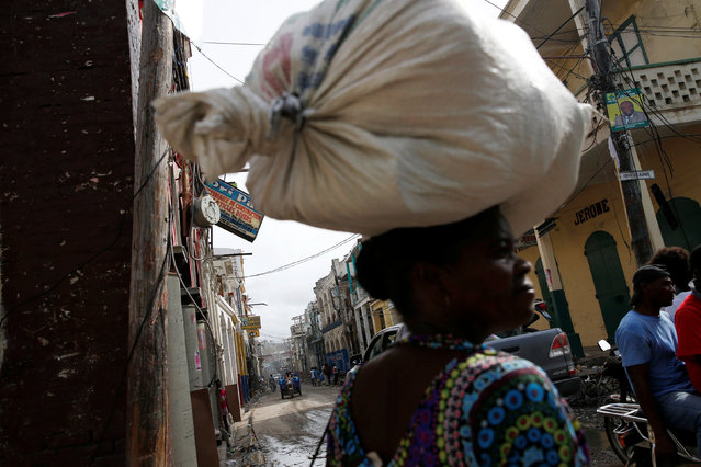 A woman carries a sack on her head while walking through the streets after Hurricane Matthew passes in Jeremie, Haiti, October 9, 2016. (Photo by Carlos Garcia Rawlins/Reuters)