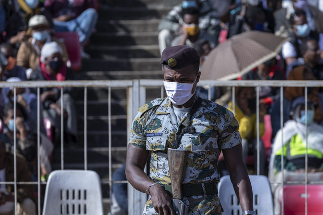 A police officer provides security as Ethiopians wait to give blood at a blood drive in support of the country's military, at a stadium in the capital Addis Ababa, Ethiopia Thursday, November 12, 2020. (Photo by Mulugeta Ayene/AP Photo)